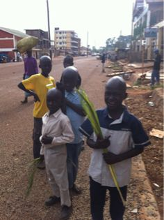 Palm Sunday in Gulu. Adults & children walking through town waving palms. #Gulu