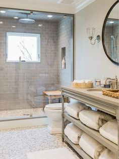 Bathroom. Gray Bathroom. Gray Bathroom Vanity. Gray bathroom features gray walls framing a round rivet mirror illuminated by uplight cage sconce over a gray French bath vanity with shelves filled with fluffy white towels topped with gray countertop white and gray penny tiled floor. A master bathroom shower boasts gray subway tile surround framing window and tiled niche alongside a ceiling mounted rain shower head over white and gray penny tile glass shower door. #Bathroom #GrayBathroom