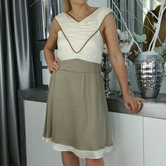 "🆕 CLASSY DRESS👗 Brand new!  This classy and chic dress feature a two layered skirt, underneath is cream, top layer is khaki brown, a cream v-neckline with tan trimming to add detail, open back adds a little sexiness to this beautiful dress. Sleeves twist in the back another fun detail.  Size Small Bust 32-34"" around Waist approx 29-30"" around  Approximately 35"" long Zips up in back  Model is 5'1"", 105lbs, 34b            Dresses"