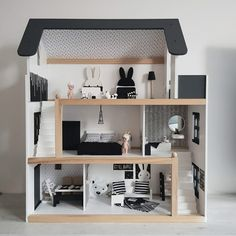 wooden doll house with black and white furniture