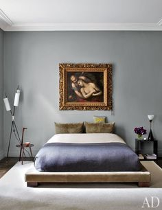 An 18th-century Italian painting hangs above a suede-upholstered platform bed hangs | archdigest.com