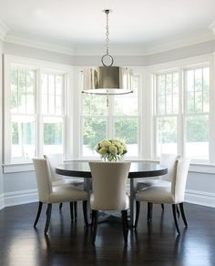Curved dining room features a dark stained round dining table lined with ivory leather dining chairs with silver nailhead trim illuminated a polished nickel drum pendant placed in front of curved windows.