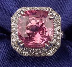 Platinum, Pink Sapphire, and Diamond Ring, c. 1950, prong-set with a cushion-cut pink sapphire with orange tones measuring approx. 11.25 x 10.68 x 9.60 mm, framed by full and single-cut diamond melee