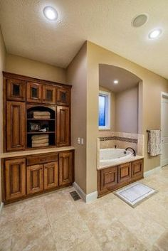 Master bathroom; built in cabinet; jetted tub; travertine tile by Donilia lemos