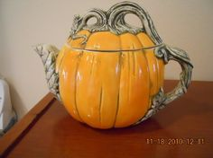 realistic orange pumpkin teapot with vine wrapping over the id to form knob, handle and spout, ceramic