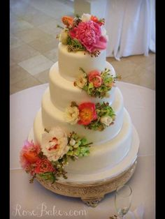 White Wedding Cake with Cascading Fresh Flowers on each Tier of the Cake .!! Very Beautiful !