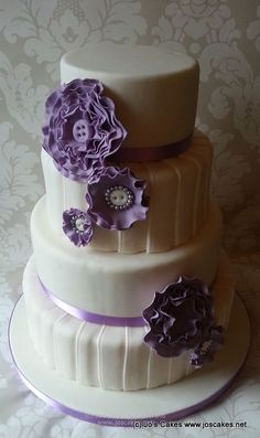 Four Tier Wedding Cake- closer to feeding 90 people. has similar ruffle flowers. imagine it in buttercream with a pearl border instead of purple ribbon
