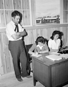 <p>Young Japanese women work in the office of the camp at Rohwer Relocation Center near McGehee, Arkansas, as stenographers and clerks, Sept. 21, 1942. Placement officer Mr. N.L. Abbot, left, dictates to Esther Ogasawara as her sister Reiko does some typing. (AP Photo/Horace Cort) </p>
