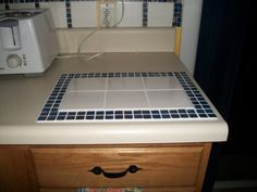 Thrifty way to cover burn mark on counter with leftover tiles and grout-cutting board and hot plate.
