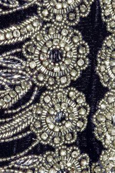Velours bleu marine Ornée de perles, cristaux et broderies, revers fendus, fente sur le devant, entièrement doublée Agrafe et fermeture à glissière dissimulées dans le dos 75 % viscose, 25 % soie ; doublure : 100 % soie Nettoyage à sec