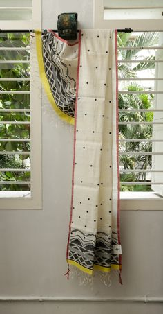 This eri silk dupatta is pure white with dot-like bhuttas in black. The selvedge is red with no border and the pallu has a pattern in black ending in a lovely yellow making it a beautiful, light co…