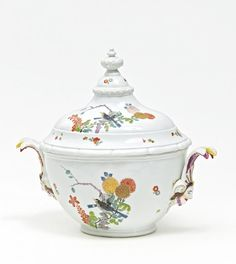 "Large Lidded Tureen with Chrysanthemums and Birds.   Meissen. Circa 1730/40.     Porcelain, enriched in colours and in gilt. Oval, bulbous form on a profiled base. Handles on the sides in the shape of female mascarons with feathered headdresses. The high-domed lid is crowned by a baluster pommel. Decorated in ""famille vert"" style with two birds sitting on branches with large chryanthemums. Height 33cm."