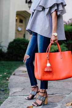 tomato red leather tote bag with ripped jeans and a ruffle top