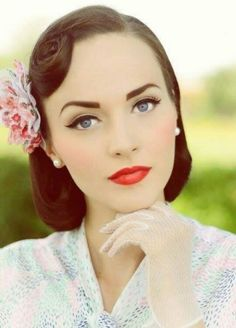 Vintage makeup look. Fresh complexion with a flush of pink blush. Thicker winged eyeliner on top of the eye with minimal eyeshadow on the bottom to elongate the eye. Very precise strong eyebrows. Red-orange lips for a more modern approach to the typical blue based red used more commonly.