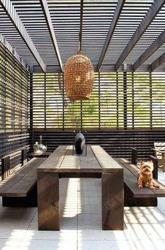 Basket Light!! Summer outdoor style!! Tres chic! Black gray and wood! Covered terrace deck veranda with modern wood dining table and benches!! Plus the cutest dog too! Dreamy modern French apartment ideas.