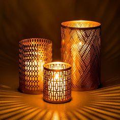 En métal délicatement perforé, ils tamisent avec subtilité la lumière d'une bougie.