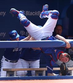 Toronto Blue Jays catcher J.P. Arencibia goes over the fence into the dugout to make an out in the eighth inning as the Toronto Blue Jays beat the Los Angels Angels 11-2. (STEVE RUSSELL/Toronto Star)