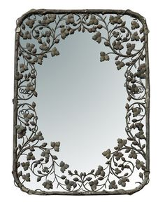 A large sized retangular mirror with an intricate leaf design surround in antiqued metal.