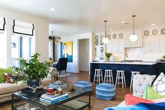 """""""this house feels so HAPPY!""""  surrounded by functional white stools, and art in the nearby dining room sets a whimsical but classy atmosphere."""