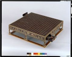 Go game board of shitan with marquetry. Wood & Bamboo. Wood faced with shitan (red sandalwood). Grids inlaid with ivory. Wood inlay: ivory, tsuge (boxwood), kurogaki (black persimmon wood), etc. Colors on ivory in lateral side design. Upper side of frame base applied with translucent material over painted decoration.
