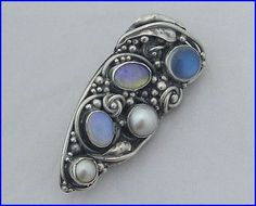 Two examples, clockwise and anticlockwise. Dorrie Nossiter. Arts and Crafts silver brooch with twined leaf, vine and berries in a long shield shape, with cabochon stones: moonstone, 2 pearls, a pale opal and another stone, possibly saphiret (glass). 5 cm long.  Sold on eBay. The seller thought it either by Sibyl Dunlop or Dorrie Nossiter but it is clearly by Dorrie.