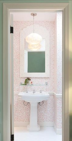 Pink powder room boasts walls clad in pink wallpaper finished with a chair rail lined with a white pedestal sink and a vintage glass shelf under a cream Moorish style bone inlay mirror lit by a feather chandelier.