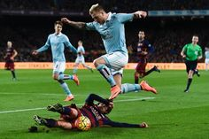 Celta's Swedish forward John Guidetti (top) jumps over Barcelona's midfielder Sergi Roberto during the Spanish league football match FC Barcelona vs RC Celta de Vigo at the Camp Nou stadium in Barcelona on February 14, 2016