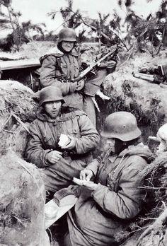 "Men of a 2.SS-Division ""Das Reich"" Maschinen Gewehr section eating rations in their prepared position, Ukraine 1944"