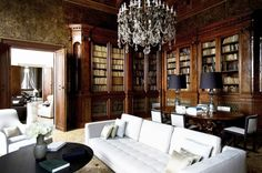 This library has dark wood cabinets, green patterned wallpaper, a chandelier, and a bright white sofa and chair.