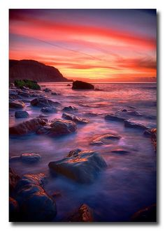 Beautifully colourful dawn sky, above the ebbing tide of Hastings beach, England