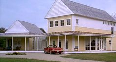 Steve Martin's yellow house in the movie Housesitter with his red car. Yellow house, copper standing seam roof, gray shingle roof, white posts.
