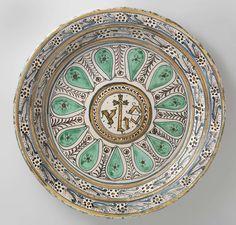 anoniem   Schotel, veelkleurig beschilderd met op het plat binnen een cirkel de letters IHS, anoniem, ca. 1450 - ca. 1475   Ronde schotel van veelkleurig beschilderde majolica. Op het plat is in het midden een cirkel geschilderd waarbinnen de letters IHS. Rond de cirkel zijn straalsgewijs druppelvormige ornamenten geschilderd, afgewisseld door een bloemenrank. Op de wand en de rand zijn bloemen bestaande uit punten geschilderd met bladeren.