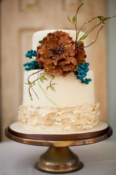 this ruffled wedding cake with dark vintage orange color flower is perfect for a outdoor fall wedding. Cake: One Sweet Slice