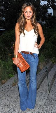 Chrissy Teigen at the Coach event in N.Y.C. sporting a pair of flare jeans and a loose tank with a golden cuff, a laid-back Coach clutch and beachy waves.