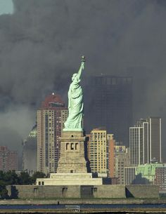 The Statue of Liberty stands in the foreground as thick smoke billows into the sky from the area where the World Trade Center stood.