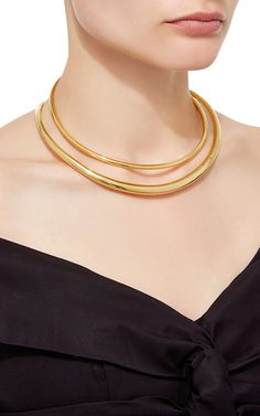 A true statement piece, this double necklace set by **Ryan Storer** is fashioned in 18K gold plated brass.