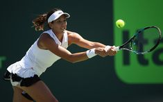 Garbine Muguruza Photos - Garbine Muguruza of Spain plays a backhand in her match against Caroline Wozniacki of Denmark at Crandon Park Tennis Center on March 27, 2017 in Key Biscayne, Florida. - 2017 Miami Open - Day 8