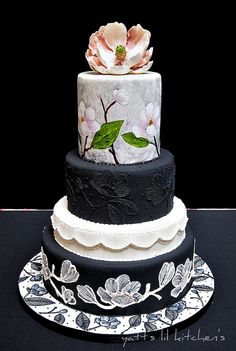 Black and white wedding cake with hand-painted magnolia flowers