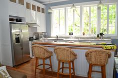 This beautiful lakefront kitchen allows plenty of sunlight in with the wall of Marvin windows over the sink.