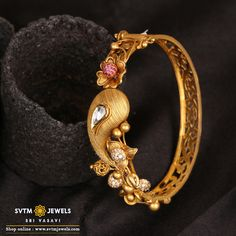 A sparkling flower blooms and mango design at the centre of this lovely bracelet, This yellow gold bracelet studded with kundan, Cubic Zircone Stones giving it a happy-bright feel. This piece of jewellery will jazz up your look and mood. Gold Chain Design, Gold Bangles Design, Gold Jewellery Design, Designer Bangles, Gold Bracelet For Women, Gold Bangle Bracelet, Gold Bracelets, Gold Bracelet Indian, Antique Jewellery Designs