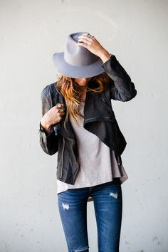Leather jacket, white tee, distressed jeans, grey hat. Effortlessly chic.