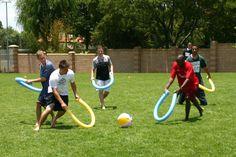 Les équipes jouent à une sorte de hockey où l'on frappe une balle de plage avec des frites de piscine.