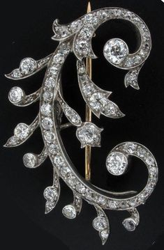 A late Victorian scroll form diamond set brooch pendant. Set in silver and gold with detachable brooch mount and in the form of a letter C. 4cm high. Case by S.J. Phillips.