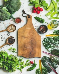#Fresh greens vegetables and grains  Fresh raw greens unprocessed vegetables and grains over light grey marble kitchen countertop wooden board in center top view copy space. Healthy clean eating vegan detox dieting food concept