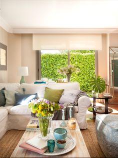 00433513. Salón con sofá blanco en L, cojines en azul y verde, auxiliar redondo y puf azul, mesa de centro madera clara 00433513
