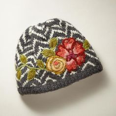 FLORA BELLE HAT - Classic chevron stripes, embroidered blossoms and beaded accents. Fleece lined. Merino wool. Hand wash. Imported. Exclusive. One size fits most adults.