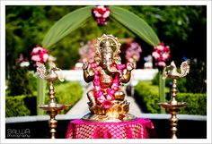 a traditional Ganesh under a perfect arch for an outdoor ceremony.