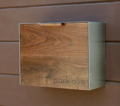 This Stainless Steel and Walnut mailbox measuring 14.5W x11.5H x 6D. This is a made to order item. The lead time is 4 weeks for the mailbox to ship. It easily attaches to an exterior wall by two keyhole brackets located on the back of the mailbox. These brackets hang from two round head