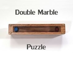 The goal of this classic marble puzzle is to be able to rest the marbles in the holes on each side of the block. Upon first contact with this puzzle, many observers will try to tilt the block to deposit the marbles in the holes. Quickly they will discover that the slope of each hole will not allow this to happen. Commonly this puzzle has a divider in the middle to keep the marbles from touching. I found that I enjoy the sound that the marbles make when clacking together and the absence of…