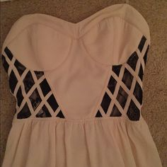 Hi-low dress w/ caged back! Hi-low dress with lace detailing on rib area. Black bands on the back super flattering, exposing some of your back. Lined underneath so it's no see through. Ivory color. Worn once. Size M Dresses